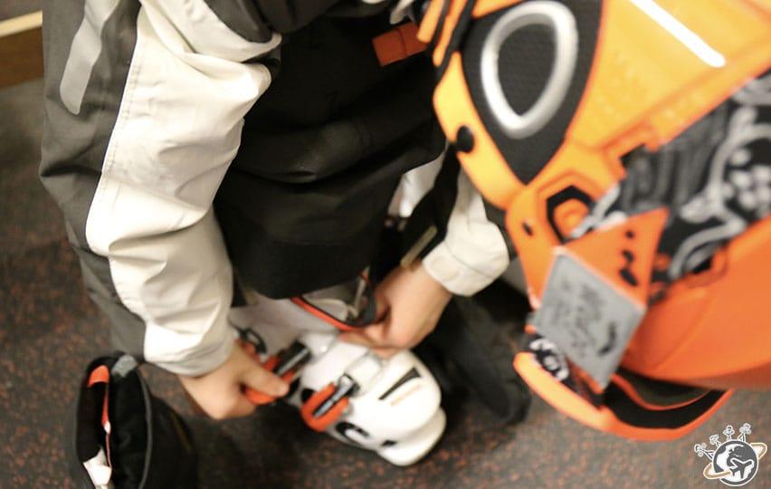 Noé met ses chaussures de ski.