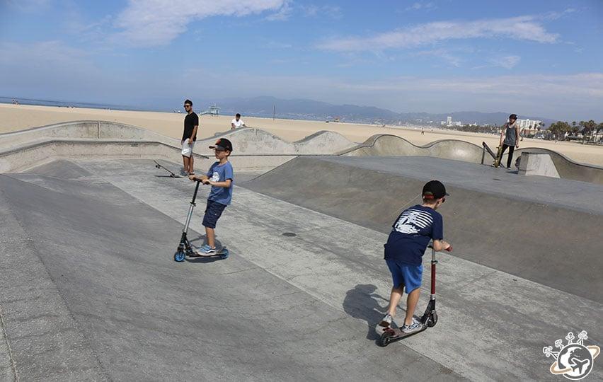 Noé et Théo en trottinette dans le skate park de Venice Beach à Los Angeles en Californie